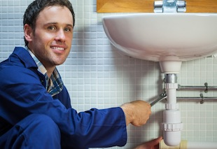 Handsome smiling plumber repairing sink in public bathroom